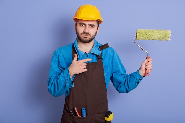 Image of bearded male builder going to paint walls