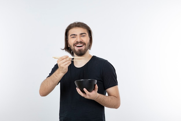 Image of bearded man holding bowl with chopsticks over a white wall.
