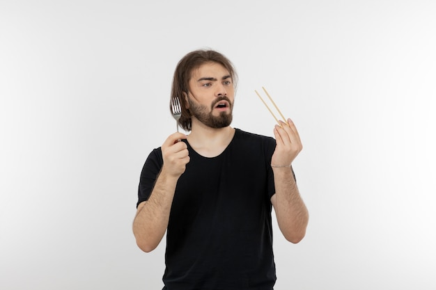 Image of bearded man holding fork over a white wall.
