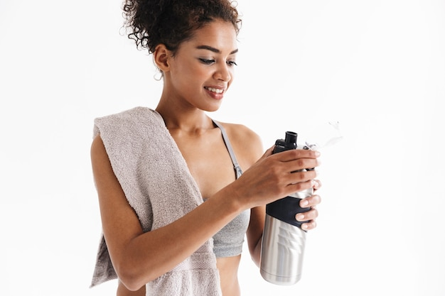 Image of a beautful young amazing sports fitness african woman drinking water holding towel.