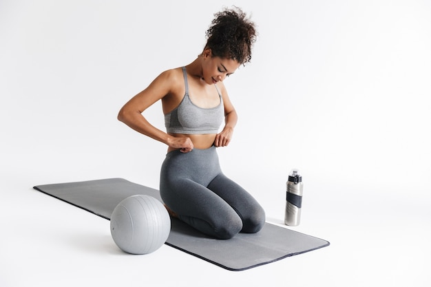 Image of a beautful young amazing sports fitness african woman posing isolated over white wall.