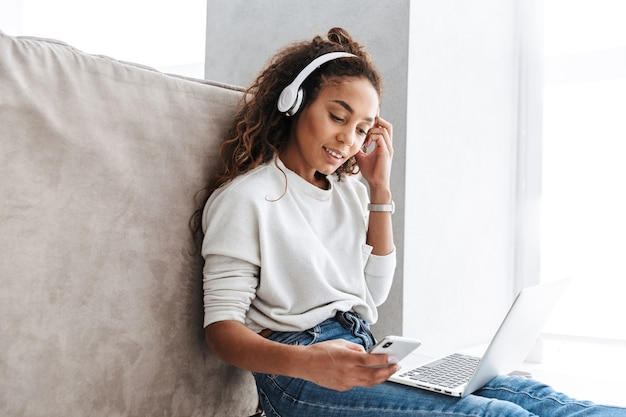 Image of beautiful african american girl wearing headphones using laptop and smartphone, while sitting on floor in bright living room