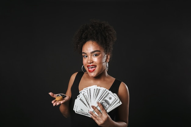 Image of a beautiful african woman posing isolated over black wall holding money and chips.