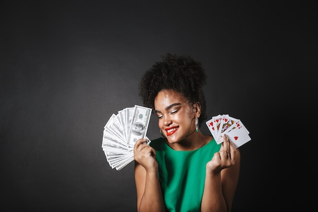 Image of a beautiful african woman posing isolated over black wall holding money and playing cards.