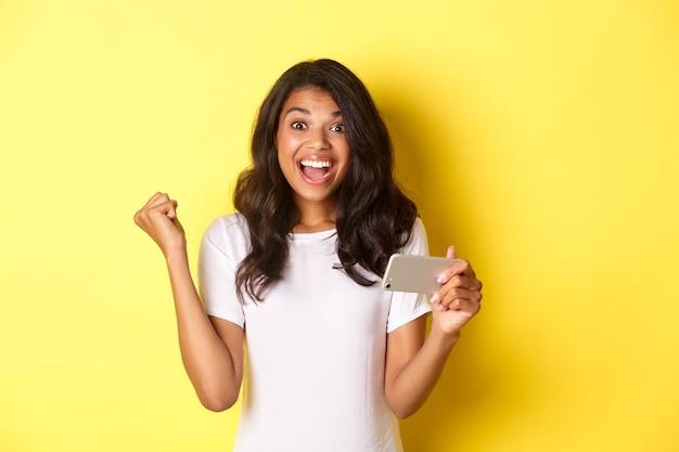 L'immagine della bella ragazza afroamericana che vince nel gioco mobile raggiunge l'obiettivo nell'app in piedi felice