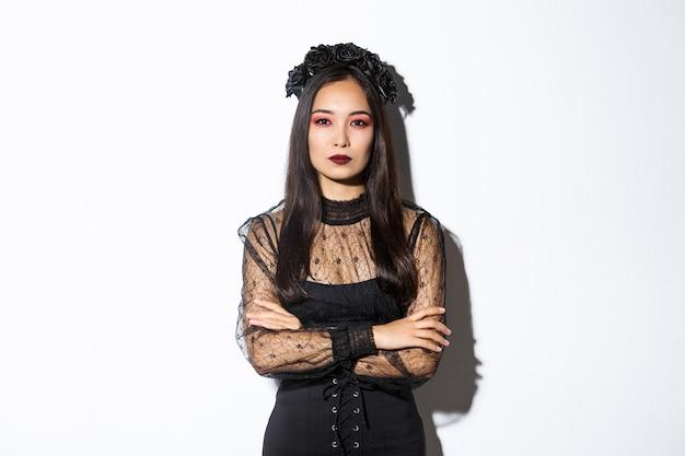 Immagine di bella donna asiatica in abito di pizzo nero e corona che sembra seria. ragazza vestita per la festa di halloween come strega cattiva, in piedi su sfondo bianco.