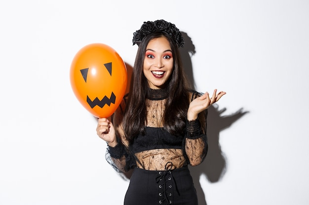 Image of beautiful asian woman celebrating halloween, wearing witch costume and gothic makeup, talking with orange balloon.