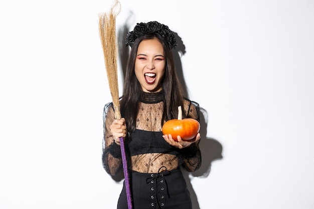 Image of beautiful asian woman dressed-up as a witch for halloween party, holding broom and pumpkin, standing over white background.