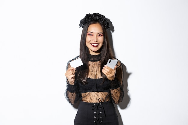 Image of beautiful asian woman in gothic lace dress and black wreath, looking aside pleased and smiling, holding mobile phone with credit card.