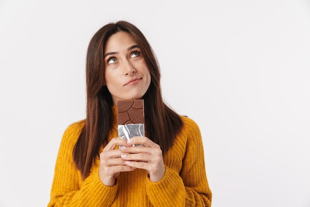 Image of beautiful brunette adult woman hesitating while holding chocolate bar isolated on white