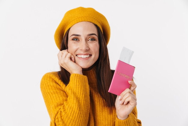 Image of beautiful brunette adult woman wearing beret hat smiling and holding travel tickets isolated on white