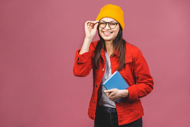 Image of beautiful brunette adult woman wearing eyeglasses smiling and reading book