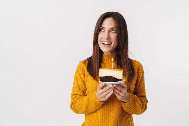 Image of beautiful brunette adult woman wearing sweater smiling and holding birthday cake isolated on white