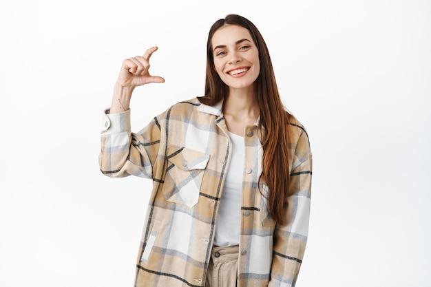 Immagine di una bella donna caucasica che mostra in mano una cosa di piccole dimensioni, un piccolo gesto, sorride compiaciuta, dimostra il prodotto in mano, in piedi su un muro bianco