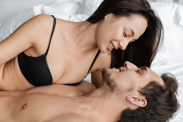 Image of beautiful couple man and woman kissing together, while lying in bed at home or hotel apartment
