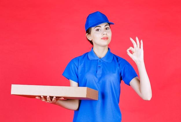 Immagine di un bellissimo corriere con scatola di cartone che dà segno ok sul muro rosso.