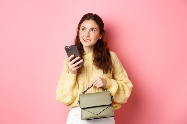 Image of beautiful female model holding purse and smartphone, looking thoughtful, thinking of best answer on message, standing against pink wall