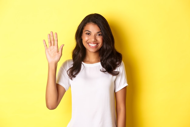 Image of beautiful and friendly africanamerican woman waiving hand and smiling saying hello greeting...