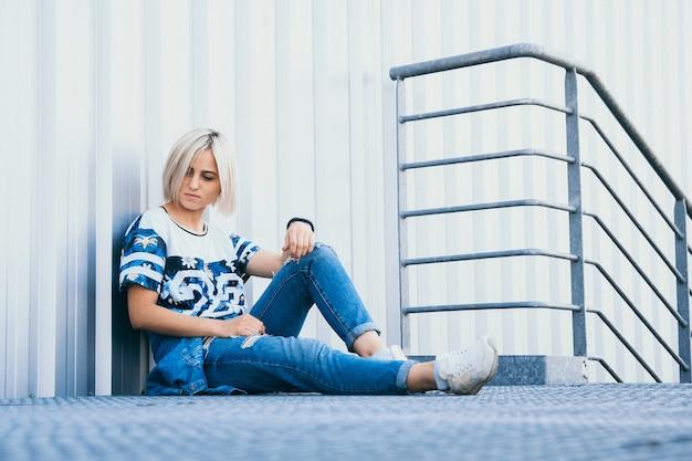 短い白い髪の美しい少女をイメージしてください。アーバンスタイルのジーンズに身を包んだ。テキストの場所。