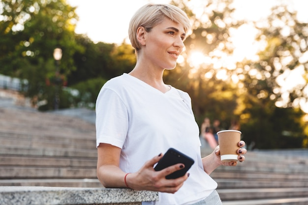 Image of beautiful happy woman with blond hair wearing casual clothing standing at city stairs, while holding cell phone and takeaway coffee
