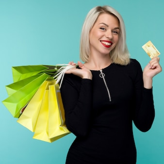Image of a beautiful happy young blonde woman posing isolated over blue wall background holding shopping bags. black friday holiday concept. sale