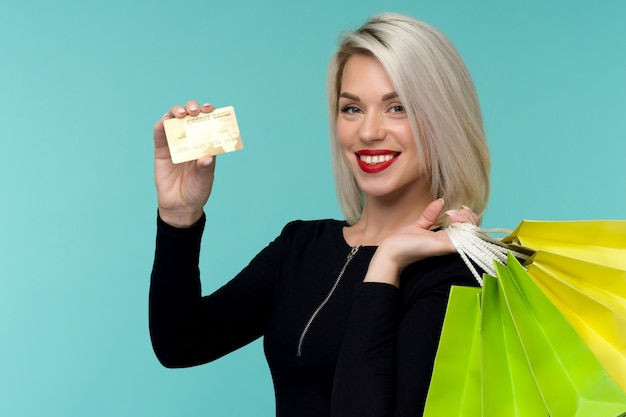 Image of a beautiful happy young blonde woman posing isolated over blue wall background holding shopping bags