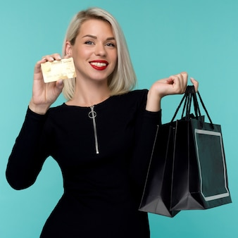 Image of a beautiful happy young blonde woman posing isolated over blue wall space holding shopping bags. black friday holiday concept. sale