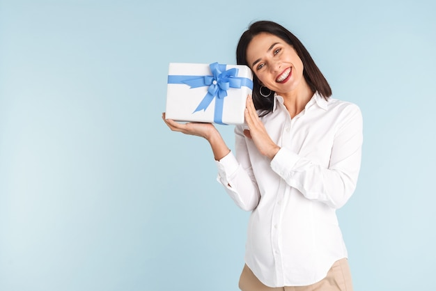 Image of a beautiful happy young pregnant woman isolated holding gift box.