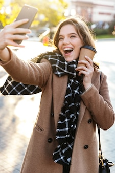 Image of a beautiful happy young woman take a selfie by mobile phone outdoors walking by street.