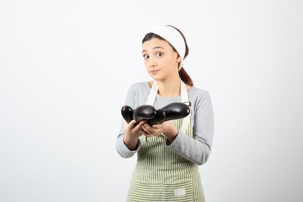 Immagine di una bella casalinga in grembiule che mostra melanzane fresche