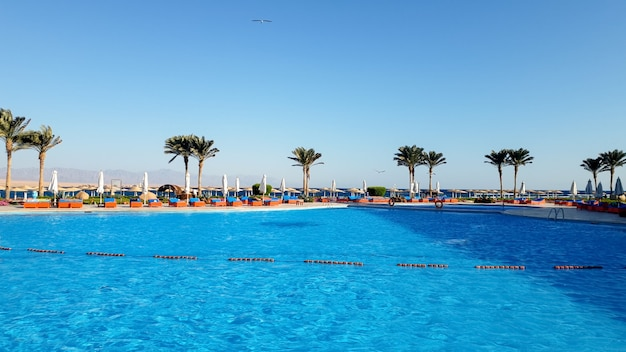 Image of beautiful outdoor swimming pool at summer hotel beach resort against blue sky