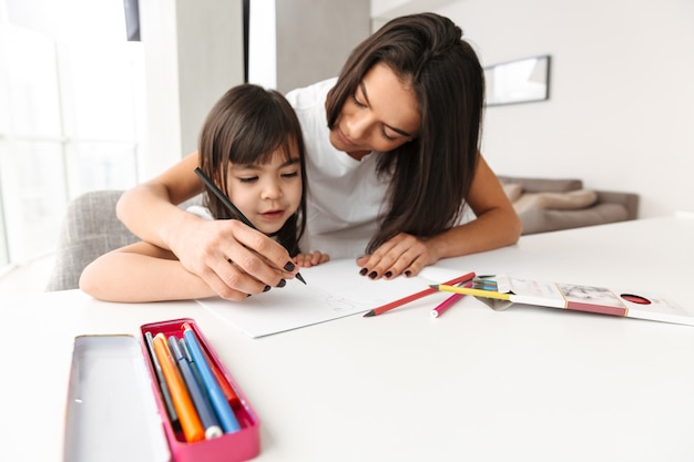Image of beautiful people woman and child taking pleasure while sitting at table in flat, and drawing picture with pencils together