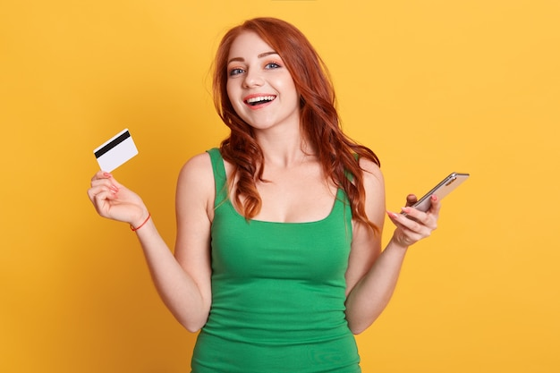 Image of beautiful red haired woman wearing green dress holding credit card and cellphone