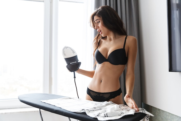Image of a beautiful shocked excited brunette woman wearing lingerie in home indoors irons shirt.