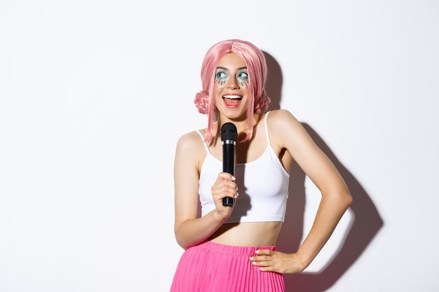 Image of beautiful smiling girl in pink wig, singing song in microphone, wearing halloween costume for party, standing.