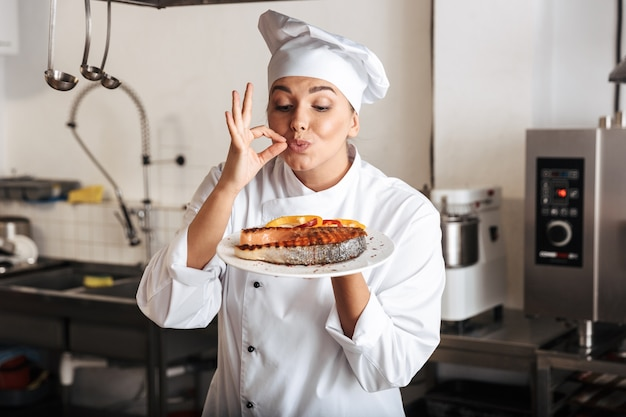 Image of beautiful woman chef wearing white uniform, holding plate with grilled fish in kitchen at the restaurant