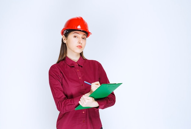 Image of beautiful woman in crash helmet writing in folder with pencil .