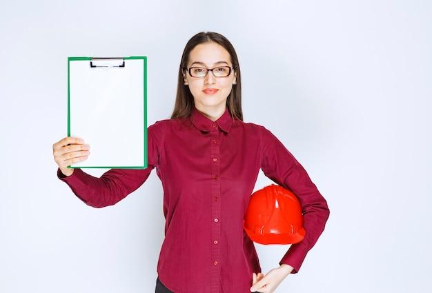 Immagine di una bella donna con gli occhiali che tiene il casco con cartella.