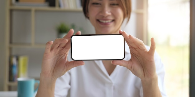 Image of a beautiful woman hold a mobile phone with blank white screen