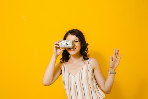 Image of a beautiful woman taking a photo with a retro camera and show gestures isolated over yellow wall