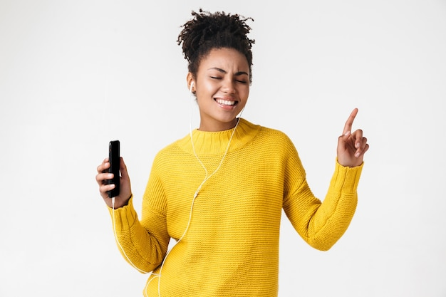 Image of a beautiful young african excited emotional happy woman posing over white wall listening music with earphones using mobile phone.