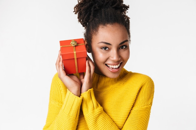 Image of a beautiful young african happy woman posing over white wall holding present box.