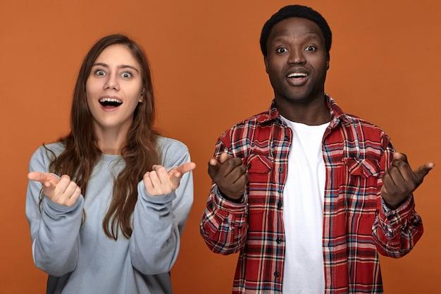 Immagine della bella giovane donna caucasica e dell'uomo africano che hanno espressioni facciali estatiche felicissime, esclamando eccitate e indicando, sopraffatte da buone notizie