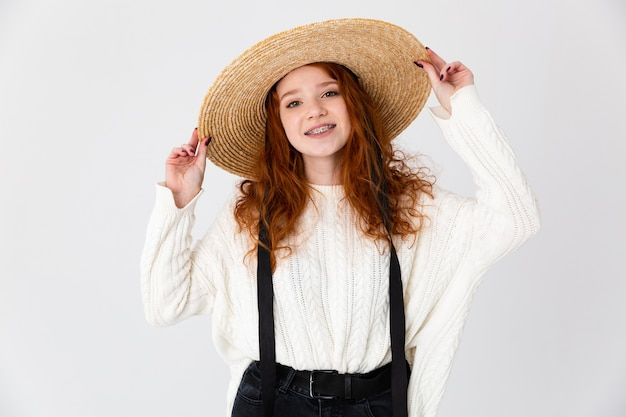 Image of a beautiful young cute girl redhead posing isolated over white wall background wearing hat.
