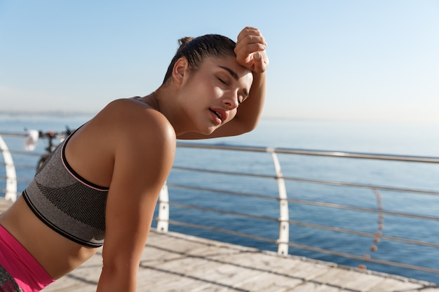 Image of beautiful young fitness woman panting and wiping sweat off forehead after jogging