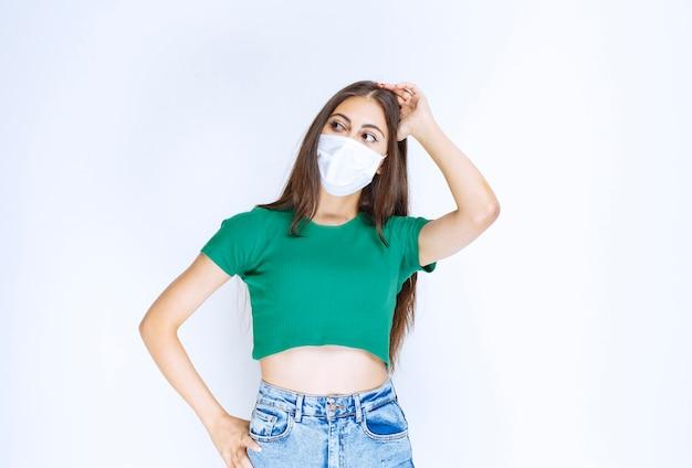 Immagine di bella ragazza in maschera medica che guarda l'obbiettivo e posa.