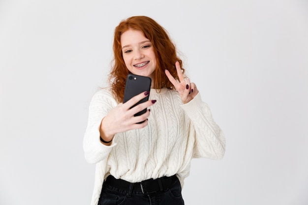 Image of a beautiful young girl redhead posing isolated over white wall background take a selfie.