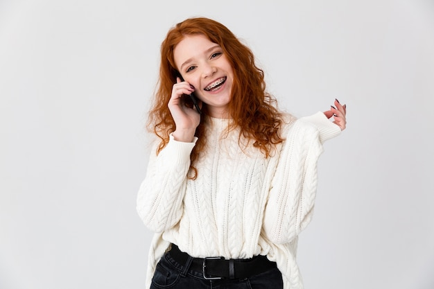 Image of a beautiful young girl redhead posing isolated over white wall background talking by phone.