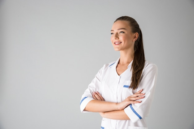 Image of a beautiful young woman cosmetologist doctor isolated over grey wall .