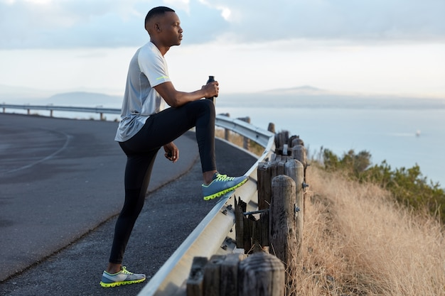Image of black motivated man holds bottle of fresh drink, dressed in tracksuit, focused into distance, admires beautiful nature, enjoys freash air, has intensive jogging exercise outdoor alone
